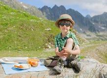 De jongen heeft picknick in bergen Royalty-vrije Stock Afbeeldingen