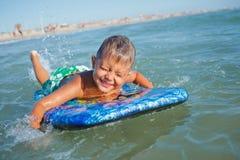 De jongen heeft pret met de surfplank Stock Fotografie