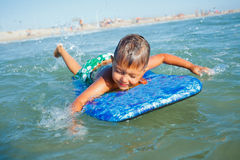 De jongen heeft pret met de surfplank Stock Foto's