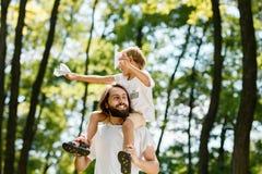 De jongen heeft pret met vader in het park op zonnige dag, allebei gekleed in de witte t-shirts De jongen zit op de schouders van royalty-vrije stock foto