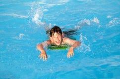 De jongen heeft pret op de surfplank in de pool Stock Foto's