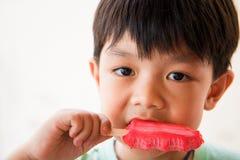 De jongen heeft tevredengesteld wanneer hij favoriet roomijs eet Royalty-vrije Stock Afbeeldingen