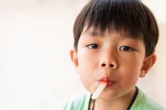 De jongen heeft tevredengesteld wanneer hij favoriet roomijs eet Stock Afbeelding