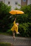 De jongen in heldere gele regenjas vliegt over de aarde met een paraplu in een hand Stock Afbeelding