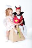 De jongen in het beeld van duivel en een meisjesengel Royalty-vrije Stock Afbeeldingen