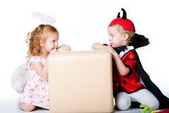 De jongen in het beeld van duivel en een meisjesengel Royalty-vrije Stock Foto's