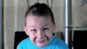 De jongen in het blauwe overhemd glimlachen stock footage