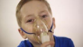 De jongen in het masker wordt het inhaleertoestel behandeld stock footage