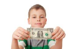 De jongen houdt één dollar in beide geïsoleerdes handen stock afbeeldingen
