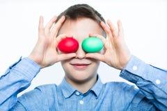 De jongen houdt een rood en groen ei Gouden ei over groene gradiëntachtergrond Voorbereiding voor de vakantie close-up royalty-vrije stock afbeelding