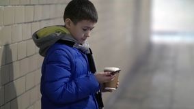 De jongen houdt in hand hete koffie in de tunnel, wachtend op iemand, vertraging, de winter stock afbeeldingen