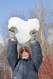 De jongen houdt in handenharten van sneeuw lucht Stock Afbeeldingen