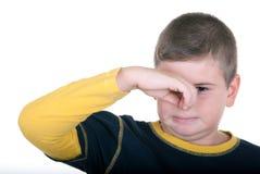 De jongen houdt neus stock foto