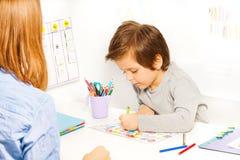 De jongen houdt potlood en kleurt de vormen op papier royalty-vrije stock fotografie