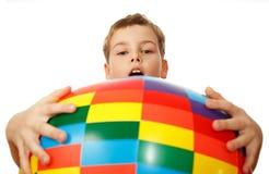 De jongen houdt vóór zich grote opblaasbare bal Stock Afbeelding