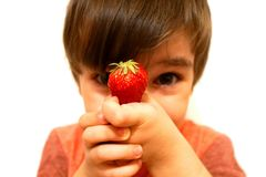 De jongen houdt in zijn hand een rode aardbei stock afbeelding