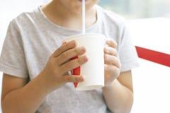 De jongen 8 jaar oude dranken melkt cocktail van document kop, snel voedselconcept stock fotografie