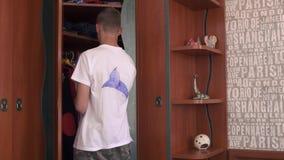 De jongen kiest kleren in de kast stock videobeelden