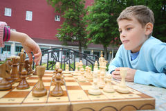 De jongen kijkt als hand van het schaakstuk van meisjesbewegingen op schaakbord stock afbeeldingen
