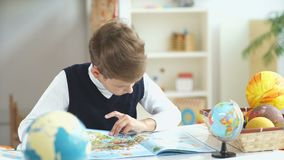 De jongen kijkt atlas met kaarten De schooljongen onderwijst aardrijkskunde stock footage