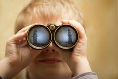 De jongen kijkt door de verrekijkers Stock Foto