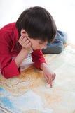 De jongen kijkt kaart Stock Foto's