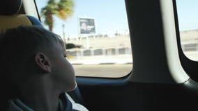 De jongen kijkt uit het autoraam stock video