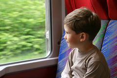 De jongen kijkt uit het venster Royalty-vrije Stock Foto's