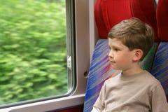 De jongen kijkt uit het venster Stock Foto's