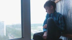 De jongen kijkt uit het venster in de regen en is droevig stock video
