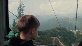De jongen kijkt uit het venster van de kabelbaan Mooi landschap, bergen Reis levensstijl stock footage