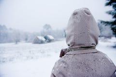 De jongen kijkt uit over een winters landschap Stock Fotografie