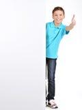 De jongen kijkt uit van de witte banner met duimen op gebaar stock fotografie