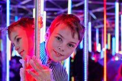 De jongen kijkt uit van hoek in spiegellabyrint Royalty-vrije Stock Foto