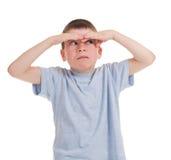 De jongen kijkt van onder palm Stock Foto