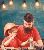De jongen, kind bezig in beschermende helm maakt met de hand, herstellend met papa Vaders hulpconcept Vader met baard stock afbeeldingen