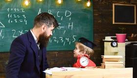 De jongen, kind in gediplomeerd GLB bekijkt gekrabbel op bord terwijl de leraar verklaart Individueel lessenconcept leraar stock afbeelding