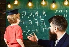 De jongen, kind in gediplomeerd GLB bekijkt gekrabbel op bord terwijl de leraar verklaart De leraar met baard, vader onderwijst royalty-vrije stock afbeelding