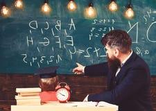 De jongen, kind in gediplomeerd GLB bekijkt gekrabbel op bord terwijl de leraar verklaart De leraar met baard, vader onderwijst royalty-vrije stock afbeeldingen