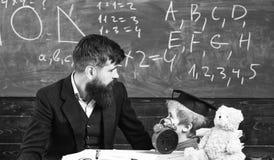 De jongen, kind in gediplomeerd GLB bekijkt gekrabbel op bord terwijl de leraar verklaart De leraar met baard, vader onderwijst stock afbeelding