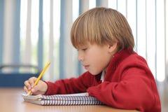 De jongen in klaslokaal het leren en concertrated binnen ogenblik stock foto's