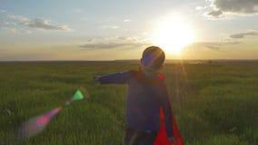 De jongen kleedde zich met een Supermankaap die op een gebied lopen, onderzoekend de zonsondergang stock video