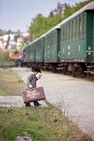 De jongen, kleedde zich in uitstekende laag en hoed, met koffer Stock Foto