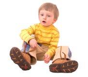 De jongen kleedt laarzen op witte achtergrond. Royalty-vrije Stock Foto's