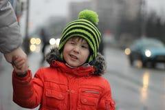 De jongen knipoogt in de hoed met bubo Weinig warm rood de kattenverstand van de jongensslijtage stock foto's