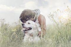 de jongen koestert affectionately zijn hond in het midden van aard stock foto