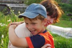 De jongen koestert zijn moeder Stock Foto