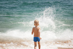 De jongen komt in de water zonnige dag Stock Foto's