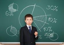 De jongen in kostuum toont grafieken op schoolraad Stock Afbeelding