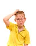De jongen krast zijn hoofd in verwarring of verwarring Stock Afbeelding